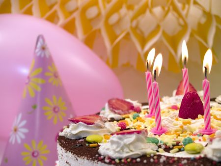 Birthday cake with candles, close up, pink balloon at background