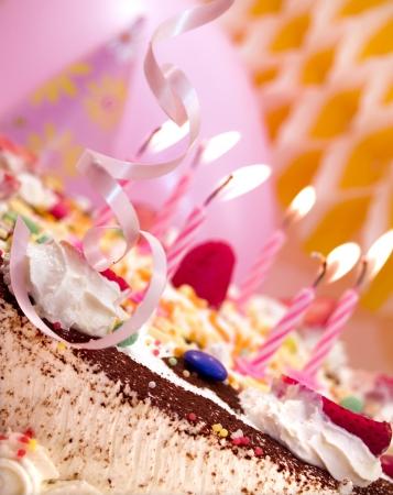Candles and pink ribbon at birthday cake, close up Stock Photo