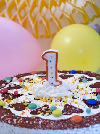 Birthday cake with number one candle, balloons at background