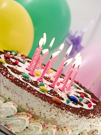 birthday cake with eleven candles, balloons at background Stock Photo