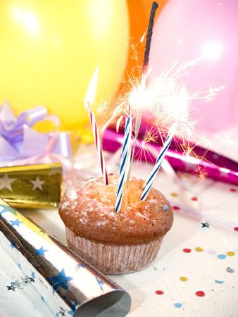 Sparklers burning at cupcake, party steamers at background Stock Photo - 387161