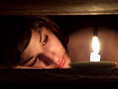 Close up of the eautiful sad girl looking at the flame