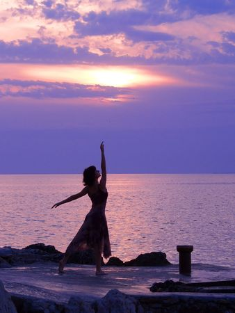 water feature: Young woman standing at ballerina pose, sunset at the background