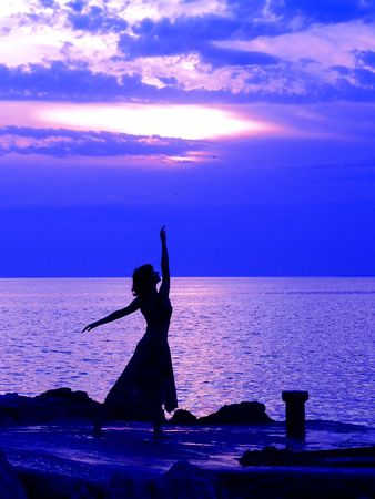 Young woman standing at ballerina pose, sunset at the background