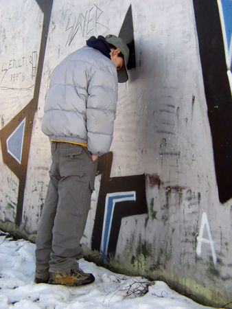 Teen boy standing against graffiti