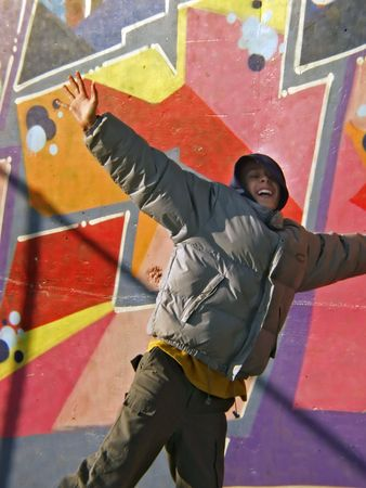 Young teen boy jump with open hands, graffittti at the background photo