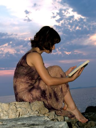 Young woman read the book sitting at on the rocks, sunset at background