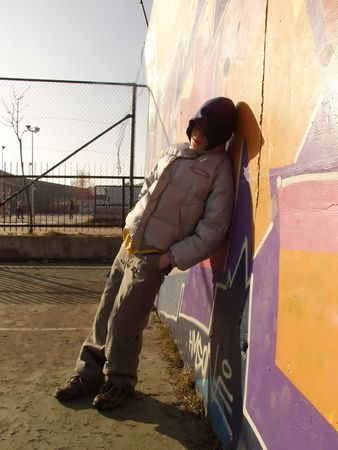 Sad teen standing against graffiti, wired playground at the background