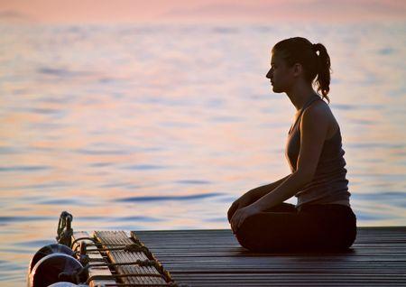 joga: Youn Woman meditating at sunrise, sea at background