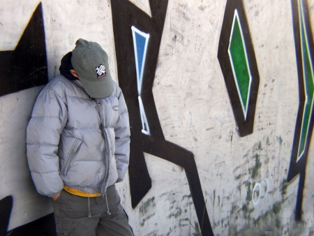 Teen boy standing in front of graffiti, head down photo