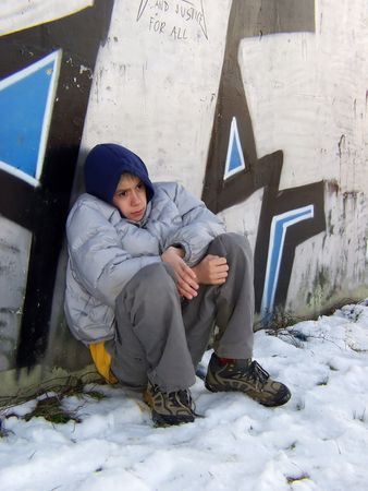 Young boy sitting against the graffiti, angry and sad face photo