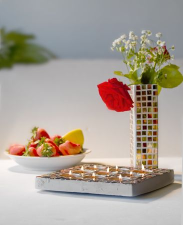 Close up of Mosaic candle holder and Mosaic vase with one rose, white background with space for text,  impression Stock Photo