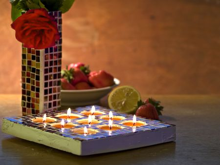 Close up of Mosaic candle holder and Mosaic vase with one rose, dark background with space for text,  impression
