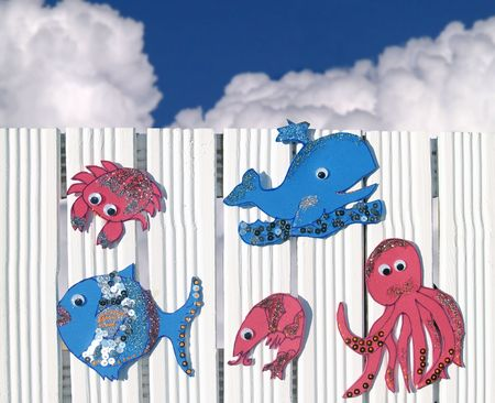 Sea creatures made of moosgummi at white fence, blue sky at background