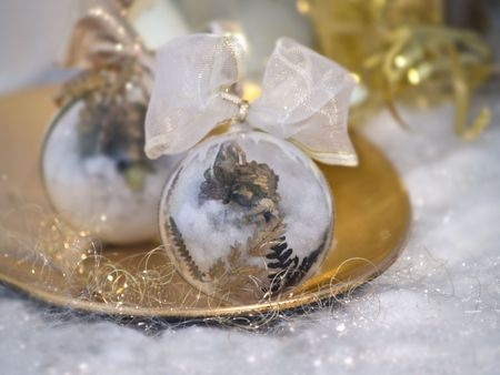 close up of two christmas balls laying at golden plate