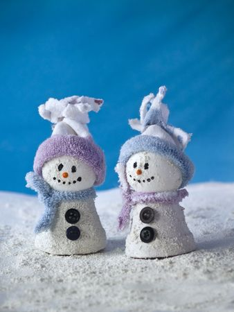 close up of two little snowman standing at blue background