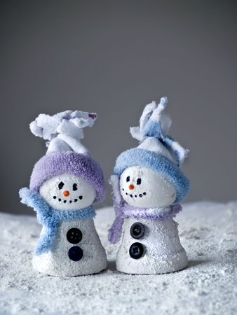 close up of two little snowman standing at gray background
