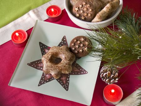 christmas table scene plate pine branches cookies and pine cones top view