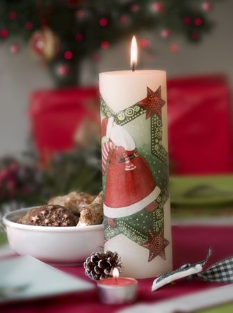 close up of christmas santa candle and bowl with cookies