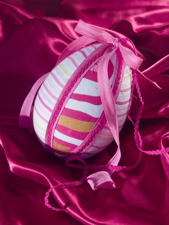 big pinky egg made of textil laying at silk background
