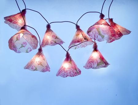 mini lights with roses motif hanging at blue background Stock Photo - 4848166