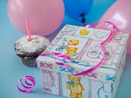 giftbox  with cute baby motifs and balloons and muffin at background
