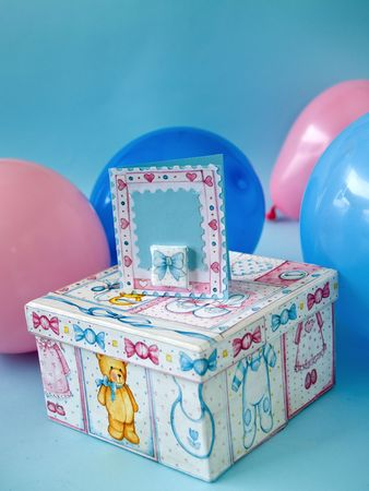 giftbox and card with cute baby motifs and balloons at background