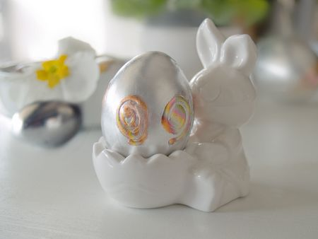 close up of silver egg standing at bunny holder