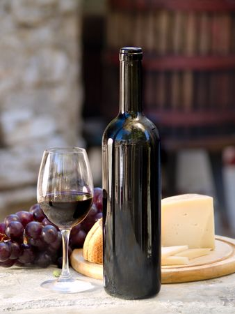 bottle and glass of red wine, grapes and cheese at the backround