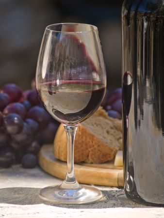 glass of red wine, grapes and cheese at the background Stock Photo