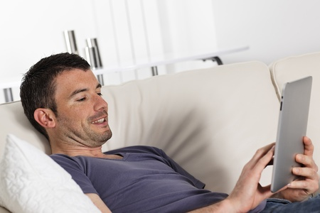 man using tablet pc on sofa at home Stock Photo - 9611257