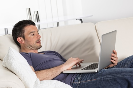 man using computer on sofa at home