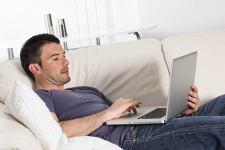 net surfing: uomo utilizzando computer sul divano a casa