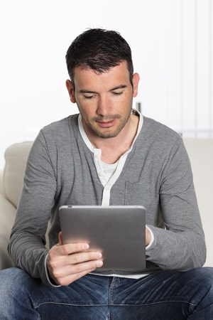 man using tablet pc sitiing on sofa at home