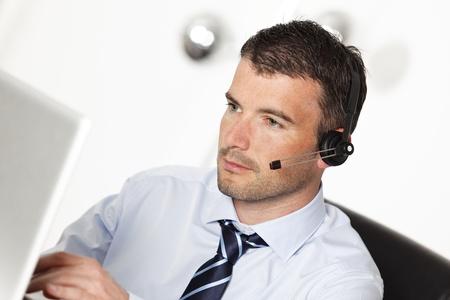 telephone headsets: hombre trabajando con auriculares y equipo de oficina