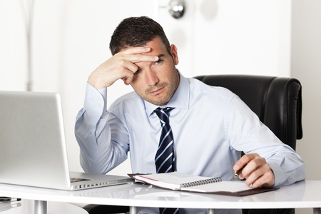 overworked: pensive man in office with computer and pen Stock Photo