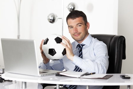 sport fan: young businessman in office with computer and ball