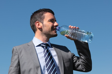 vivifying: businessman drinking water with bottle and blue sky
