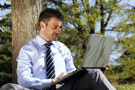young businessman working on laptop in a park photo