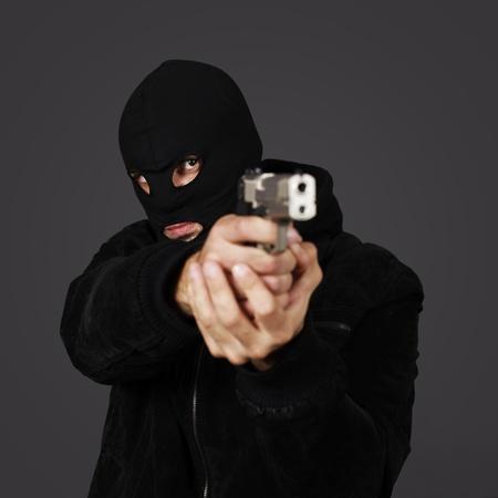 sicario: hombre vestido negro con pistola en estudio