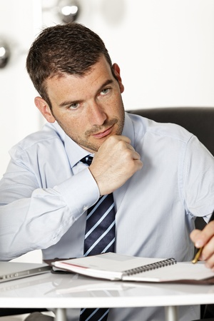 young pensive businessman in office with pen