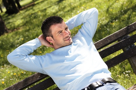 late thirties: relaxed man on a bench in a park