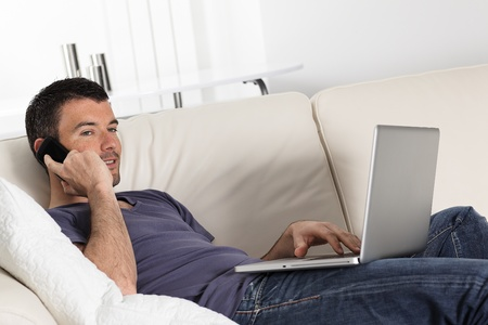 surfing the internet: beautiful young man on sofa with computer and phone
