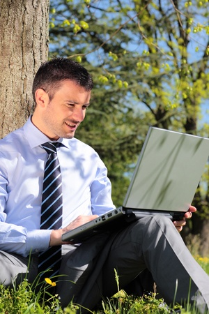 com: young businessman working with laptop in a park Stock Photo