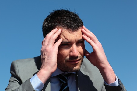 businessman with head in the hands in blue sky photo