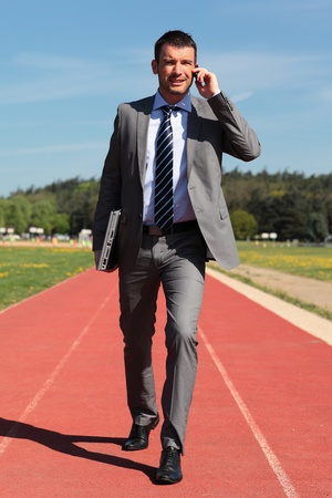 businessman with phone and laptop on a running track photo