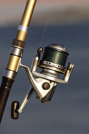 spinning reel: fishing reel on the beach with sunlight