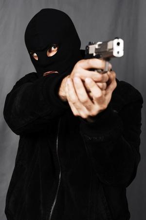 dea: black dressed man and gun in studio