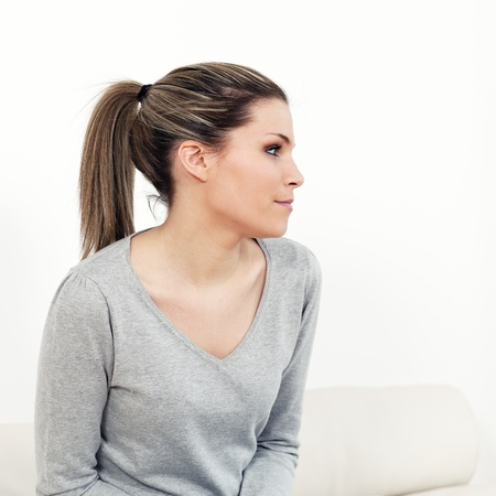 forehead: Portrait of young pensive woman at home Stock Photo