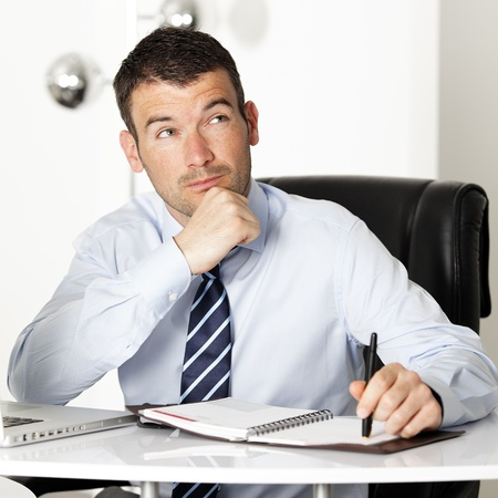 pensive businessman looking up in office with pen photo